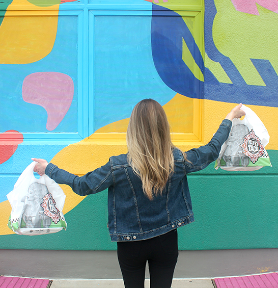 woman with Velvet Taco takeout looking at mural